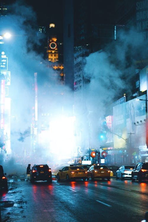 Modern city road covered with steam at night