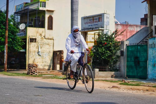 Full body faceless Asian male wearing white long dress and headscarf riding bicycle through asphalt road on rural street