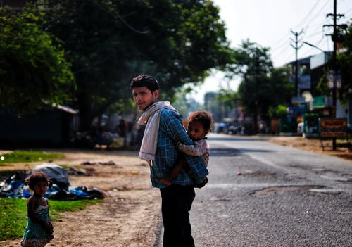 Serious ethnic father piggybacking daughter on poor district street