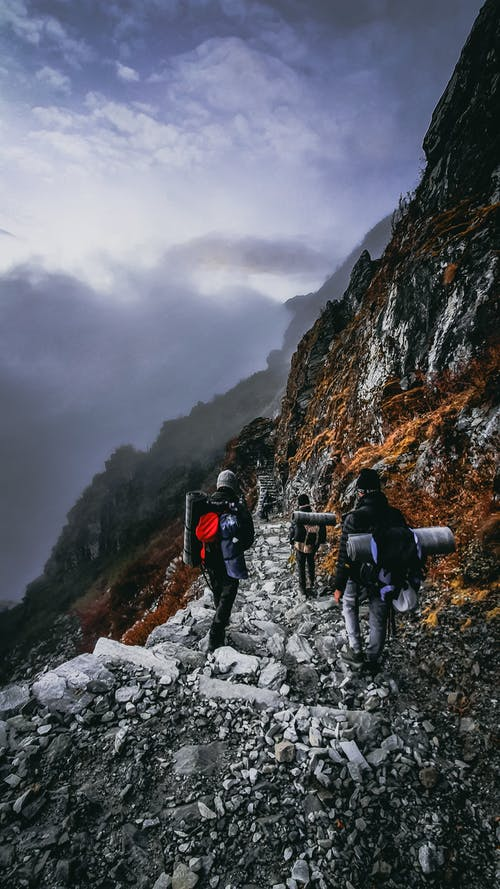 Back view of unrecognizable travelers with backpacks climbing up mountain slope on cloudy day