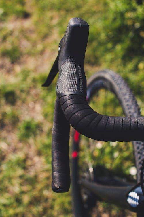 Handlebar of modern bicycle on grass