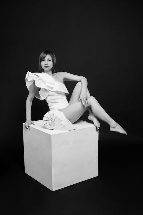 Barefoot graceful woman on cube in black studio