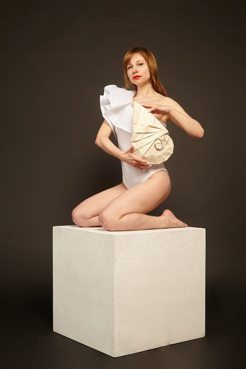 Woman in white bodysuit with handmade figure