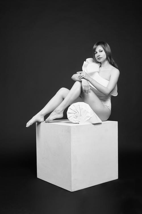 Sensual woman in white bodysuit on cube