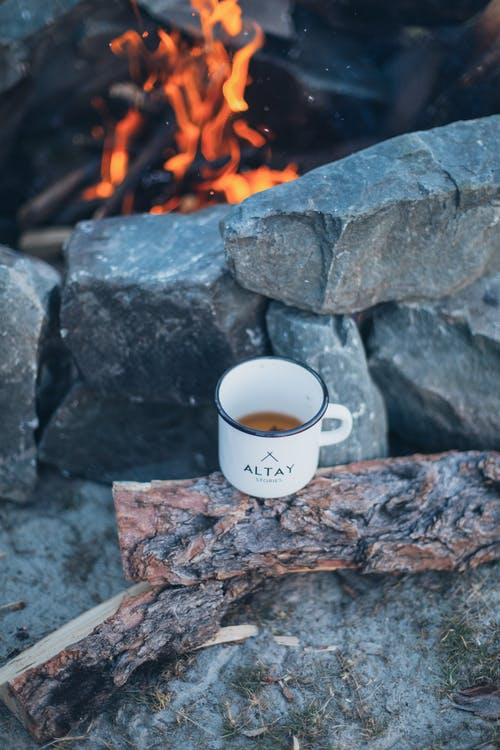 Burning fire and tea cup on log