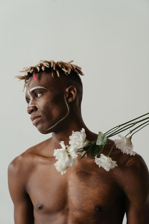 Topless Man With White Flower on His Ear