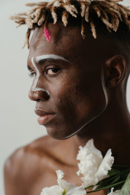 Man With White and Pink Flower on His Ear