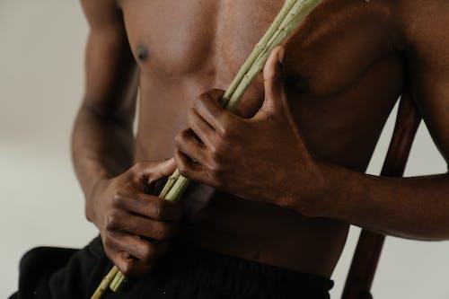 Man in Black Shorts Holding Green Stick