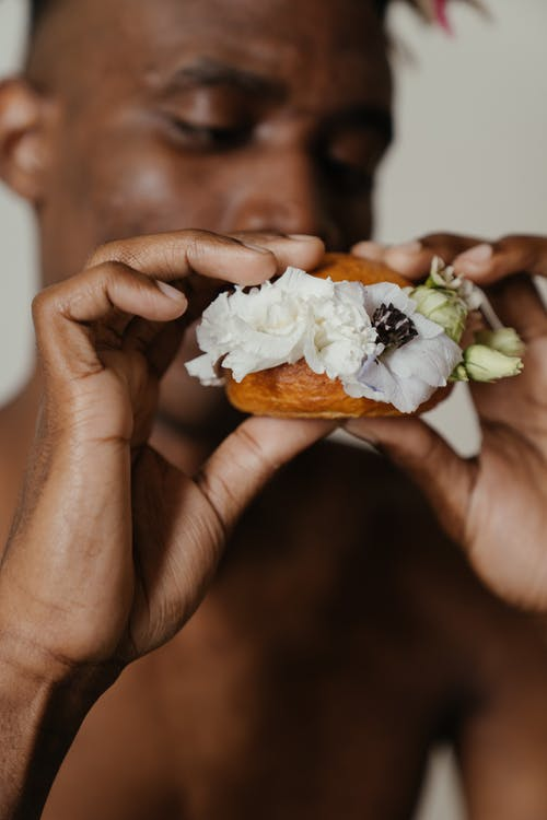 Person Holding White and Brown Pastry