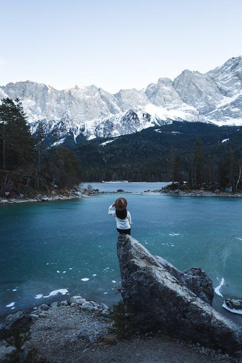 Man in White Shirt and Black Pants Sitting on Rock Near Lake
