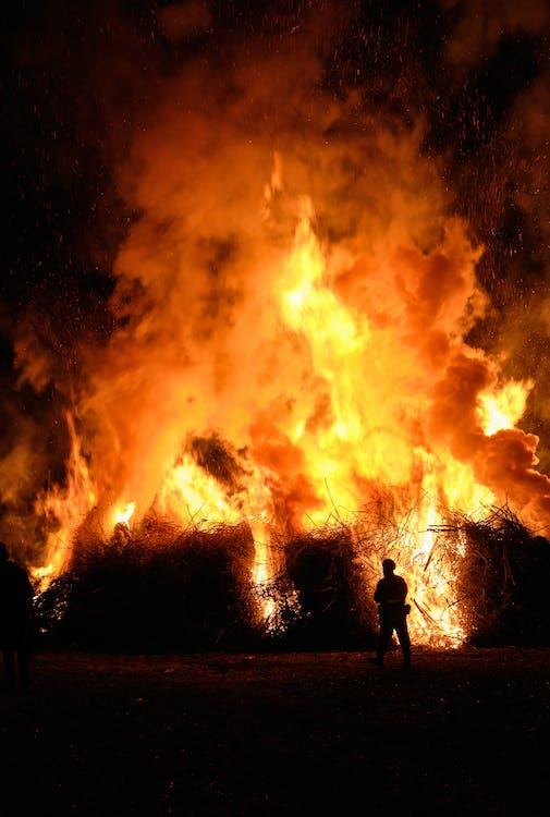 Silhouette of Man Standing Near Fire