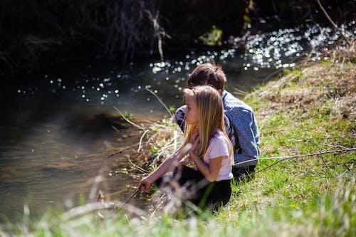 Photo of Kids Sitting Near River