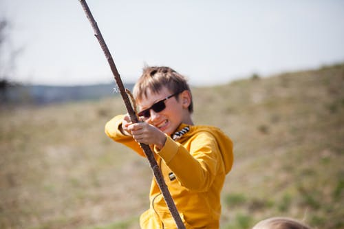 Boy in Yellow Jacket Holding Brown Stick