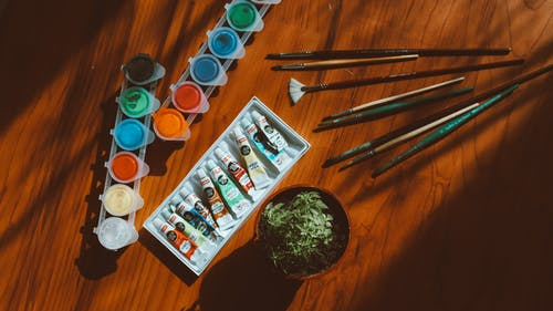 Top View Photo of Art Materials on Wooden Table