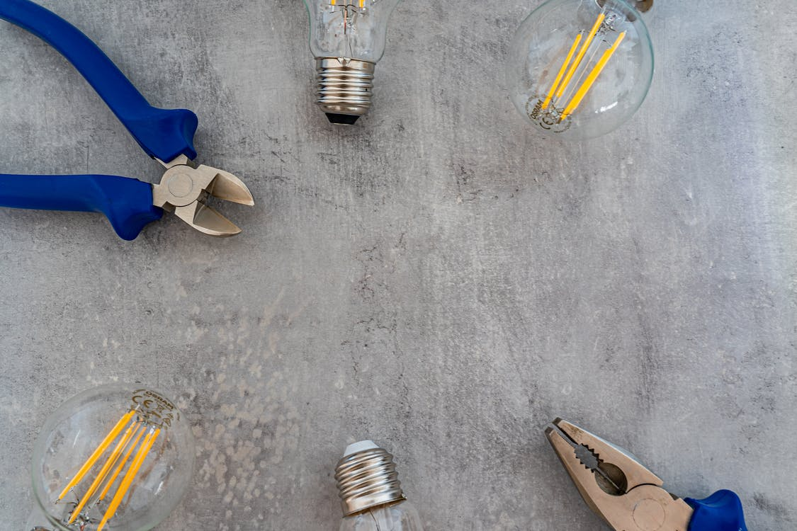 Photo of Incandescent Lightbulbs and Pliers on Gray Surface