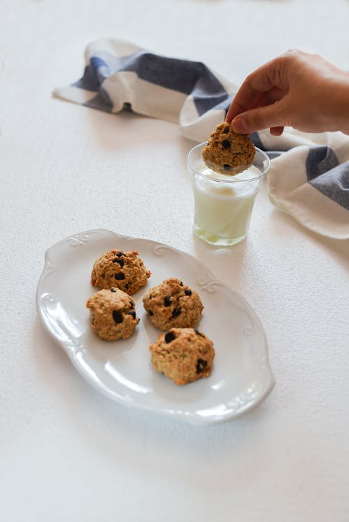 Photo of Person's Hand Dipping Cookie on Glass With Milk