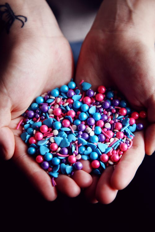 Person Holding Blue and Red Beads
