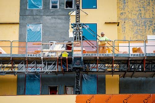 Builder on lifting platform during site works