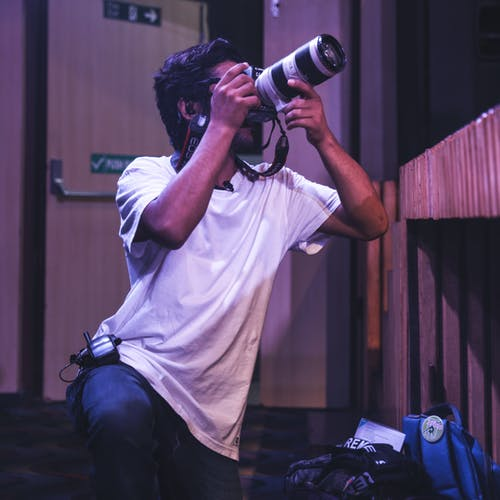 Man in White T-shirt and Blue Denim Jeans Holding Black Dslr Camera