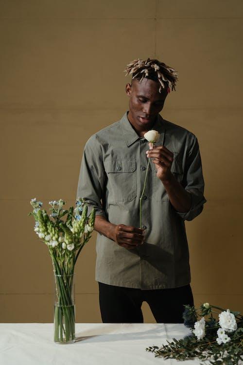 Man in Gray Dress Shirt Holding White Rose