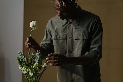 Man in Gray Dress Shirt Holding White Flower