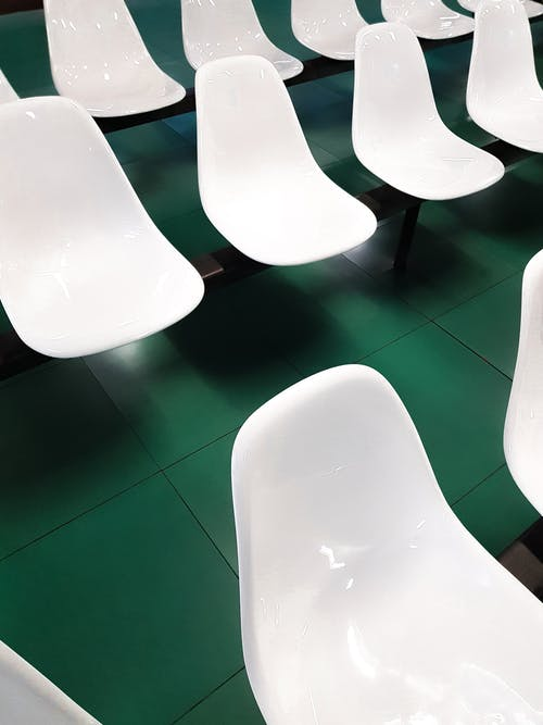 From above of white plastic seats placed in rows inside of hall with green tiled flooring