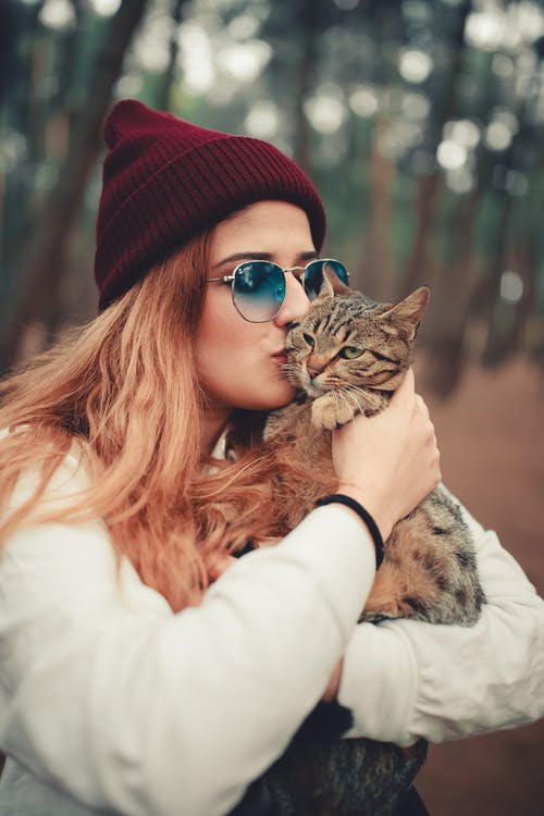Photo of Woman Kissing Her Tabby Cat