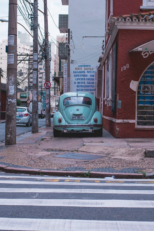 Blue Volkswagen Beetle Parked Beside Red Building