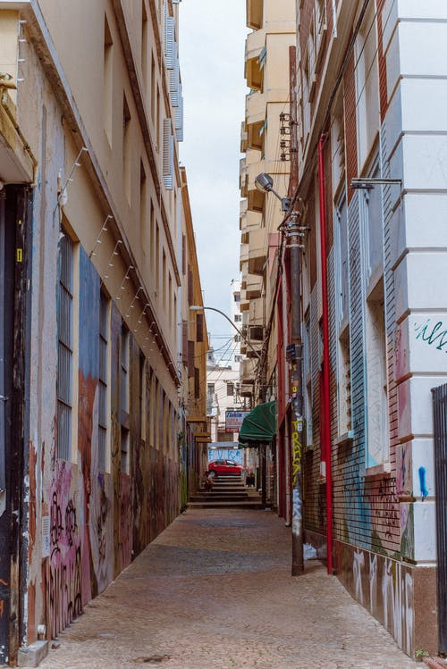 Photo of Alley Between Brown Concrete Buildings