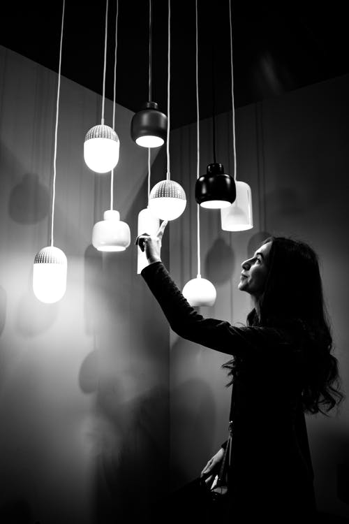 Grayscale Photo of Woman Touching Pendant Lights