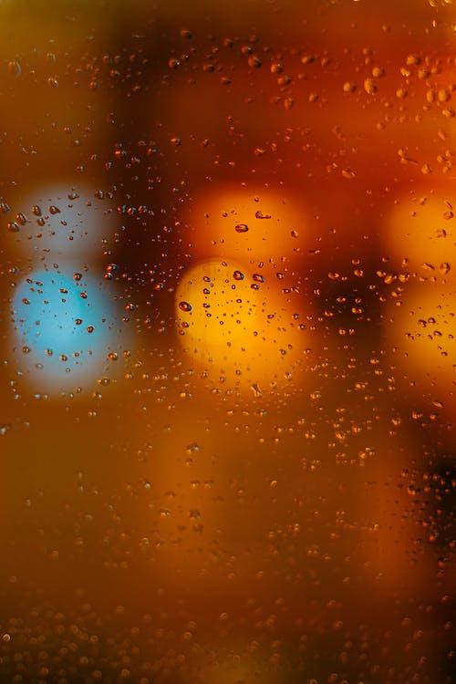 Street lights behind wet glass window