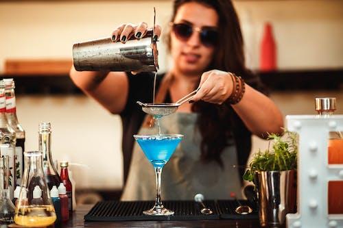 Cool female bartender making cocktail