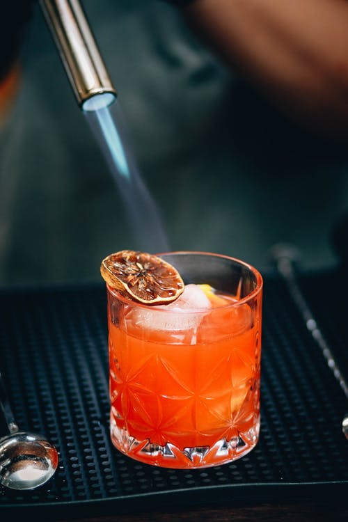 Bartender burning citrus slice on cocktail