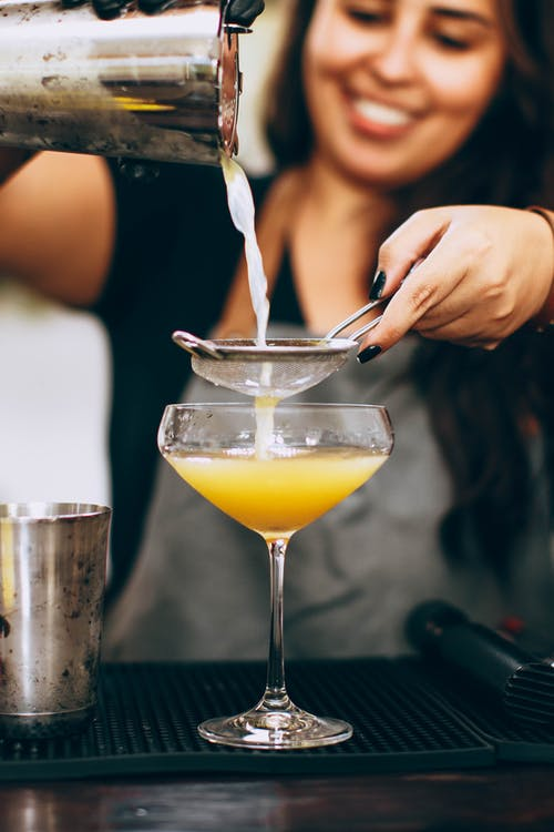 Woman Pouring Yellow Liquid From Drink Mixer