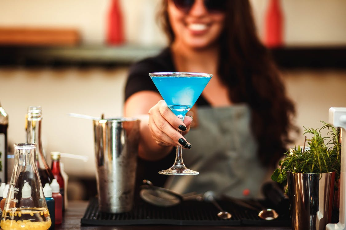 Photo of Woman Holding Cocktail Glass With Blue Liquid