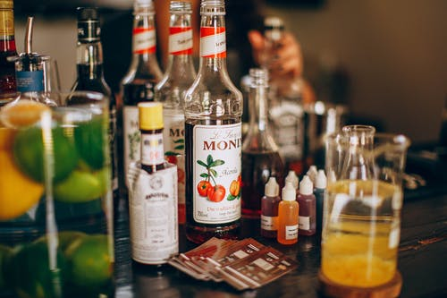 Assortment of syrups and alcohol on bar counter