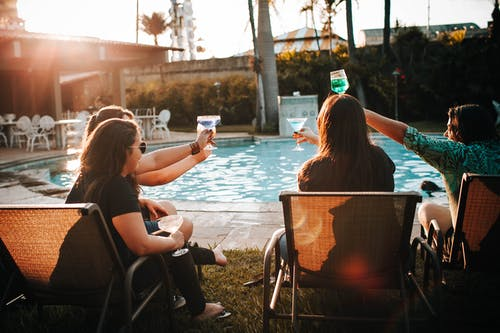 Unrecognizable tourists with cocktails spending vacation near swimming pool
