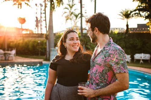 Photo of Couple Smiling While Standing on Poolside