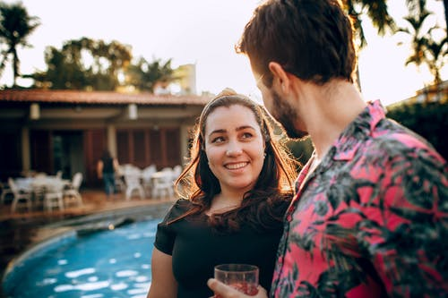 Happy girlfriend with man chatting during summer vacation