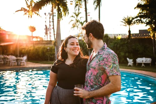 Man and Woman Standing Beside Swimming Pool