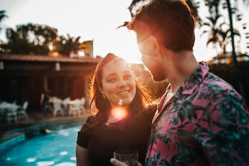Happy couple speaking near swimming pool in sunshine in evening