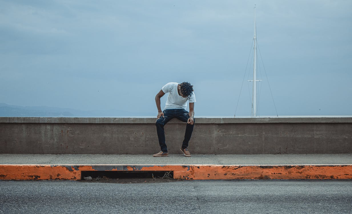 Photo of Man Sitting on Concrete Wall Barrier