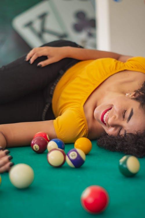 Woman in Yellow Shirt Lying on Billiard Table