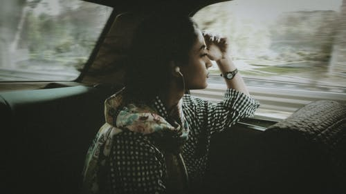 Side view of pondering young ethnic lady listening to music in earphones while sitting leaned on hand near window inside automobile and looking away