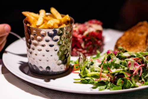 Close-Up Photo of Salad and Fries on White Plate
