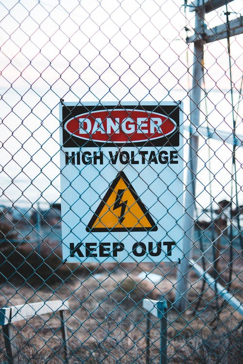Signboard with of high voltage on fence