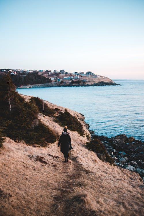 Unrecognizable woman walking on mountain path near ocean