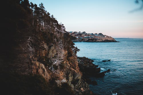 Rough cliff near blue sea under sky in evening