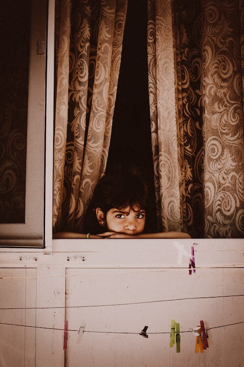 Ethnic boy looking out window near curtain with decor