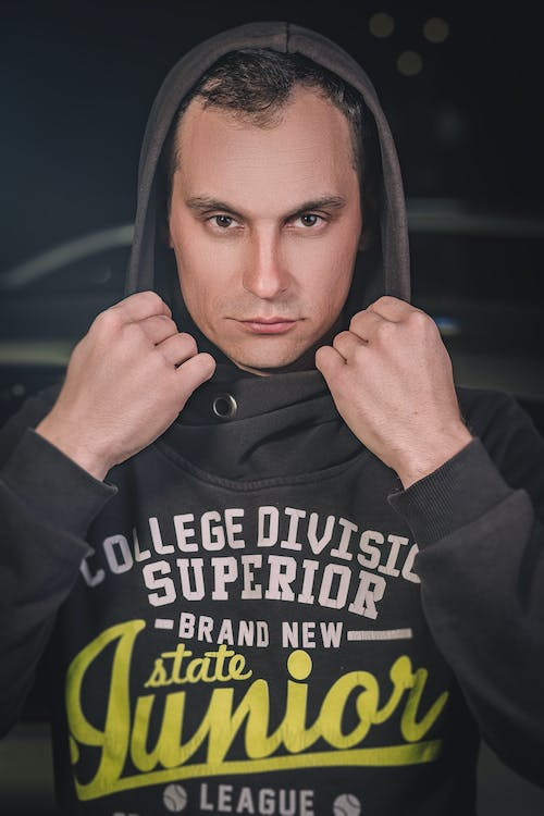 Confident male in black hoody with frown look standing in dark place and looking at camera